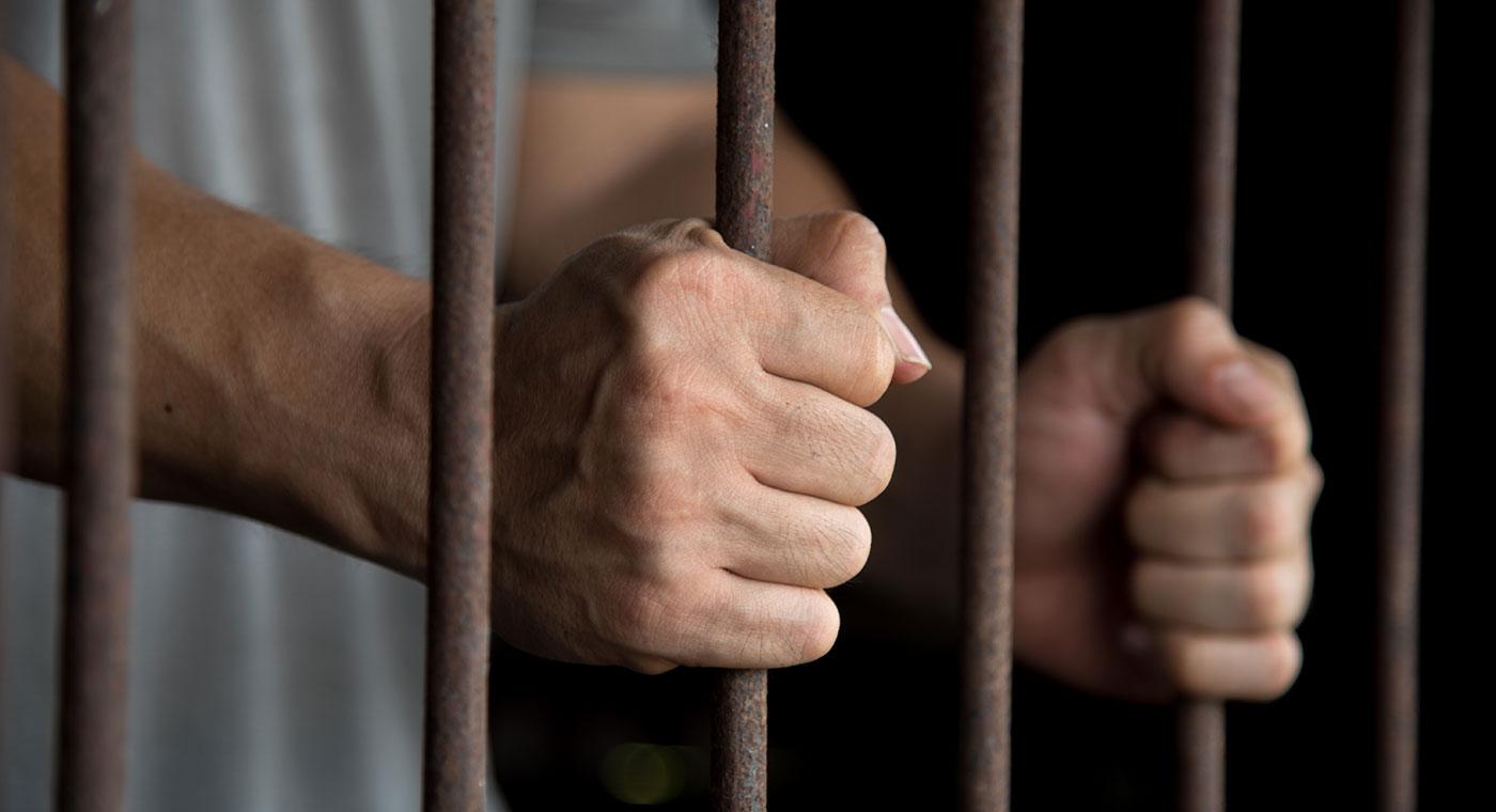 Photo of a man behind bars.