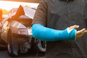A man with a cast standing in front of a totaled vehicle, needing a Car Accident Lawyer in Peoria IL