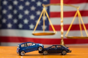 Two toy cars crashed into each other in front of a scale and American flag, representing a Car Accident Lawyer in Peoria IL