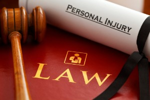 A law book with a gavel and piece of paper that reads personal injury