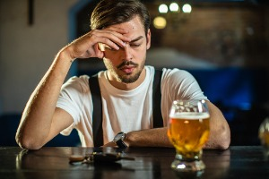 A man thinking about drinking and driving, who may need the assistance of a DUI Lawyer in East Peoria IL if he does